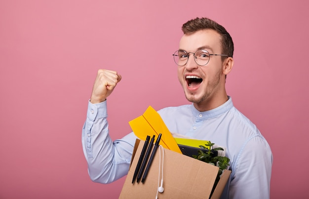 Un chico guapo joven se levanta en rosa con una caja de cartón con bolígrafos, planta y avión de papel