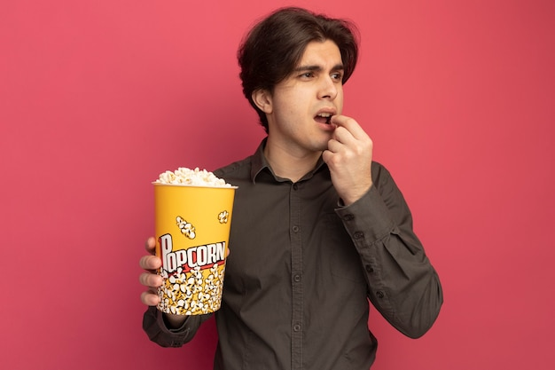 Chico guapo joven mirando a un lado con camiseta negra sosteniendo y tratando un cubo de palomitas de maíz aislado en la pared rosa