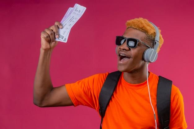 Chico guapo joven con mochila y auriculares sonriendo feliz sosteniendo billetes de avión