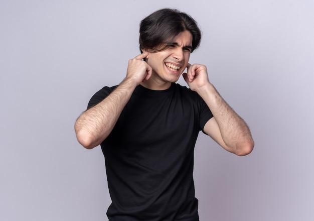 Chico guapo joven molesto con camiseta negra cerrando los oídos aislados en la pared blanca
