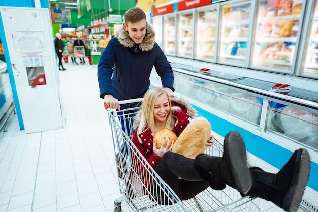 Chico guapo joven monta a una niña en un supermercado en un carro