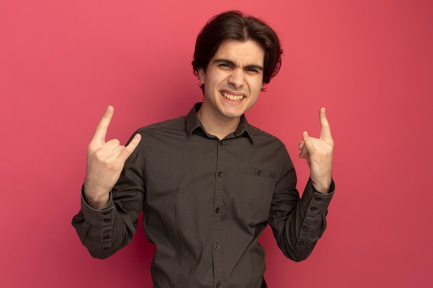 Chico guapo joven sonriente con camiseta negra que muestra gesto de cabra aislado en la pared rosa