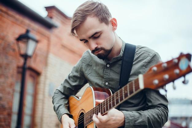 Chico guapo joven toca la guitarra, recoge un acorde, músico callejero