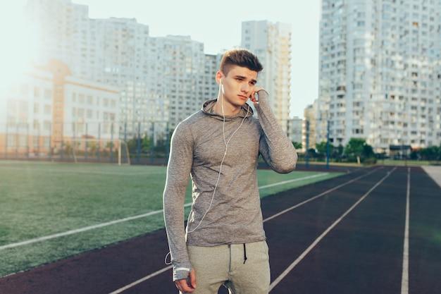 Chico guapo joven en traje de deporte gris en pista de atletismo en el fondo de edificios en la mañana. viste traje deportivo gris, auriculares. él está mirando a un lado.