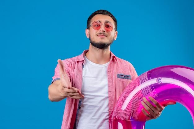Chico guapo joven viajero con gafas de sol con anillo inflable mirando a la cámara con una sonrisa ofreciendo mano haciendo gesto de saludo sobre fondo azul