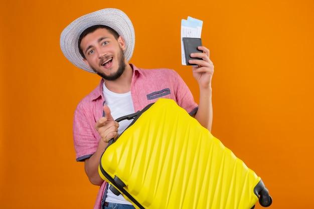 Chico guapo joven viajero en sombrero de verano con maleta y boletos aéreos mirando a la cámara salió y feliz sonriendo alegremente listo para viajar de pie sobre fondo naranja