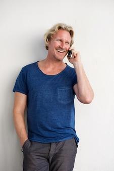 Chico guapo mayor de pie junto a la pared blanca y hacer una llamada telefónica