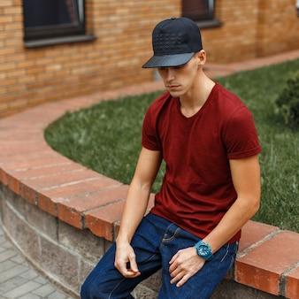 Chico guapo de moda con una gorra de béisbol negra se sienta cerca de un edificio de ladrillo