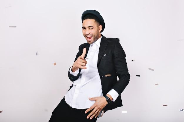 Chico guapo moderno fresco en traje divirtiéndose en oropel. celebraciones, fiesta, buen humor, alegría, disfrutar, sonreír, artista divertido.