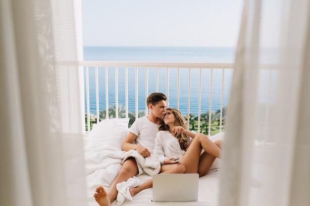 Chico guapo morena abrazando a su encantadora esposa, acostado en la cama con portátil blanco. hermosa joven pareja pasar tiempo juntos en la mañana perezosa, besándose en el balcón con vistas al mar