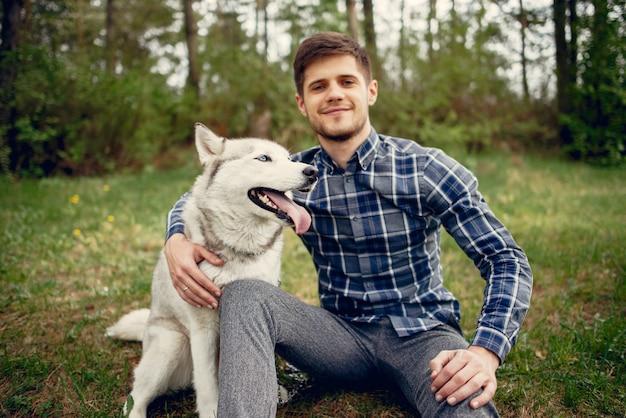 Chico guapo en un parque de verano con un perro