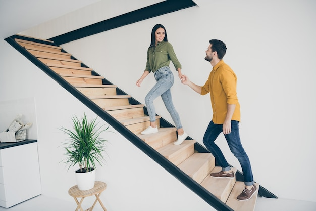 Chico guapo de perfil de longitud completa y su bella dama subiendo las escaleras en un piso nuevo y moderno