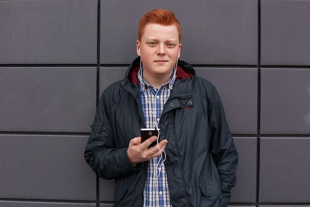 Un chico guapo positivo con el pelo rojo con pecas en la cara con chaqueta negra