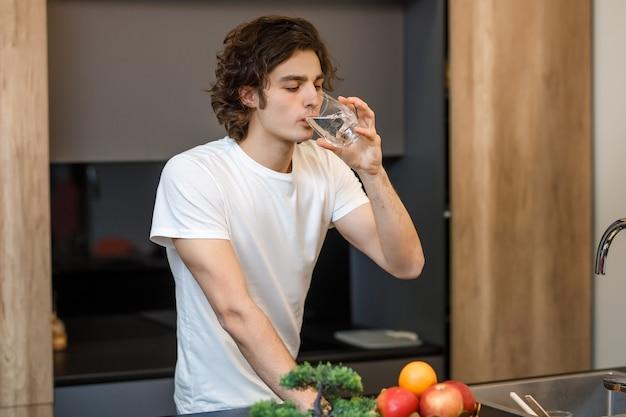 Chico guapo quédate en la cocina moderna, bebiendo un vaso de agua por la mañana