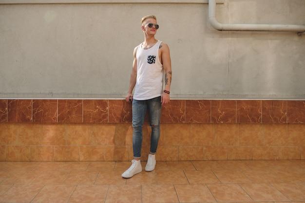 Chico guapo rubio hipster en elegante ropa de verano en la calle