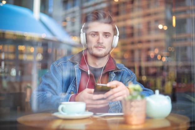 Chico guapo sentado en un bar, escuchando algo con auriculares
