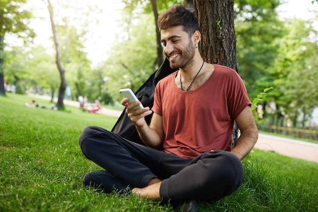 Chico guapo sentado en el parque, apoyado en el árbol y usando el teléfono móvil, desplácese por la aplicación de redes sociales, charlando