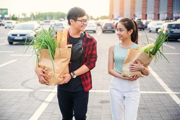 Chico guapo sonriente con gafas y linda chica delgada van con dos grandes bolsas de papel llenas de varios productos comprados en la tienda