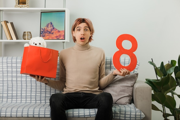 Chico guapo sorprendido en el día de la mujer feliz sosteniendo el número ocho con bolsa de regalo sentado en el sofá en la sala de estar