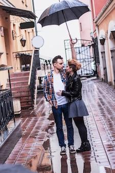 Chico guapo y su novia parados bajo un paraguas en un día lluvioso. historia de amor