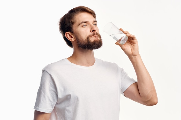 Chico guapo con un vaso de agua sobre un fondo blanco camiseta modelo vista recortada