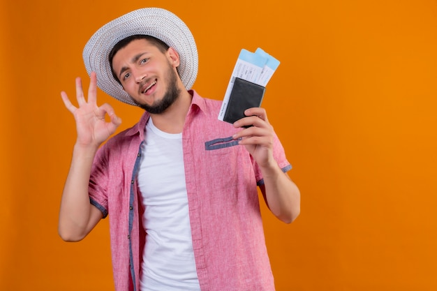 Chico guapo viajero joven con sombrero de verano con billetes de avión mirando a la cámara salió y feliz sonriendo alegremente haciendo bien firmar listo para viajar de pie sobre fondo naranja