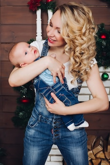 Chico con hermosa mamá rubia abrazando en casa decorada para navidad