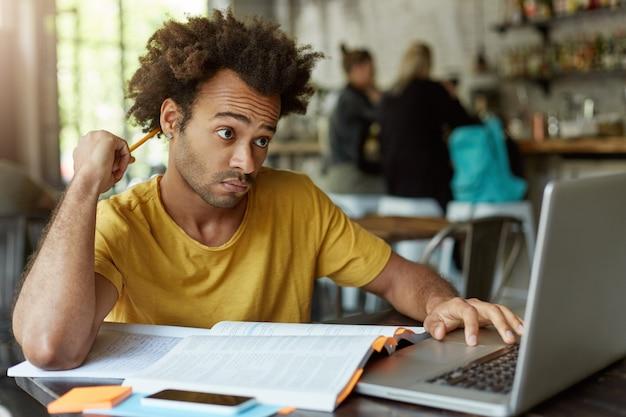 Chico hipster con cabello tupido sentado en la cantina de la universidad rascándose la cabeza con un lápiz tratando de entender cómo lograr una tarea difícil usando internet para ayudar