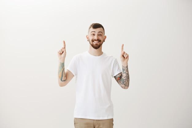 Chico hipster emocionado apuntando con el dedo hacia arriba y sonriendo feliz