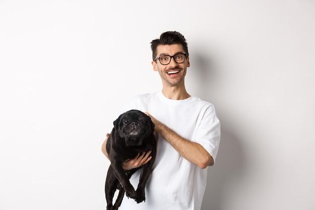 Chico hipster feliz en gafas perro mascota y sonriendo. lindo pug negro disfruta pasar tiempo con el propietario, mirando satisfecho, de pie sobre fondo blanco.