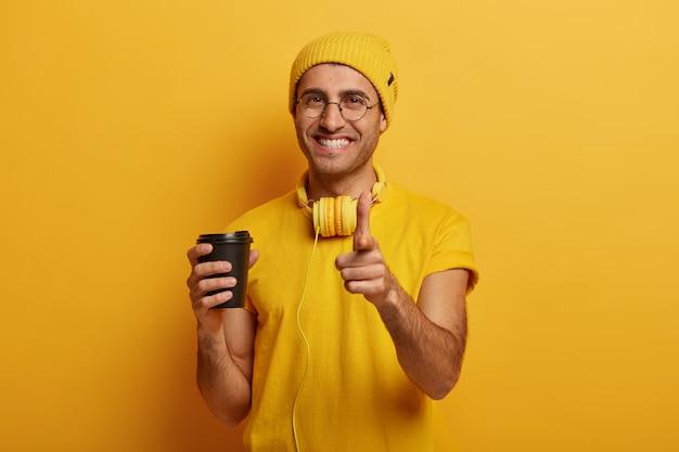 Chico hipster guapo positivo señala con el dedo índice, hace una elección, usa sombrero amarillo y auriculares