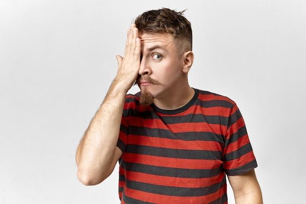 Chico hipster de moda en elegante camisa con rayas rojas y negras posando en estudio gris, cubriendo un ojo, habiendo examinado su vista. personas, lenguaje corporal, signos, gestos y símbolos