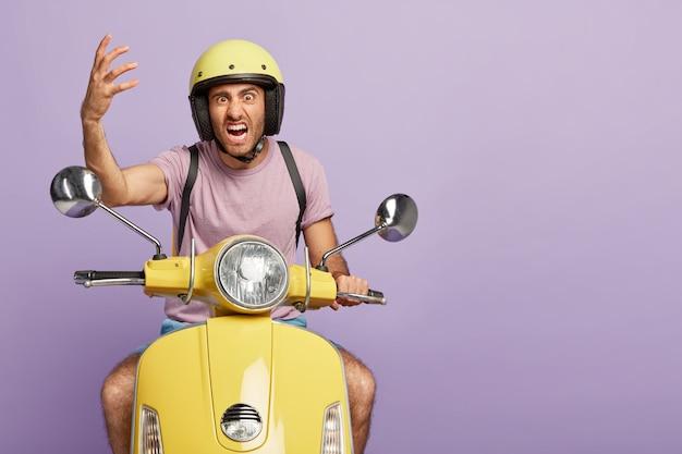 Chico impaciente irritado con casco conduciendo scooter amarillo