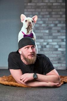 Chico inconformista con su bonito bulldog francés vestido con corbata de lazo contra la pared de ladrillo en el fondo. concepto de amor de mascotas