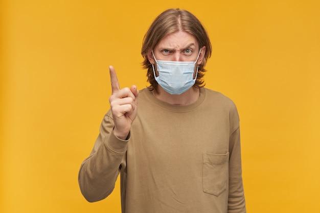 Chico infeliz con cabello rubio y barba. vistiendo suéter beige y mascarilla protectora médica. amenaza con un dedo. aislado sobre pared amarilla