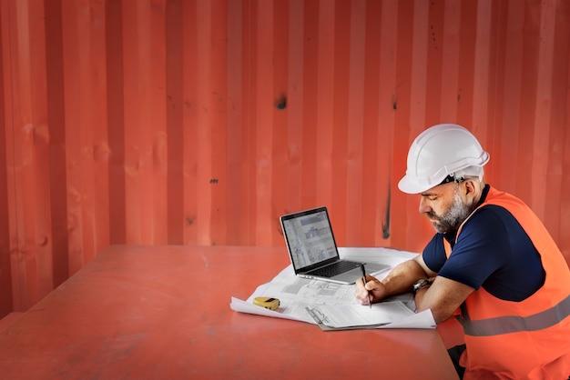 Chico de ingeniería trabajando sobre el proyecto en el sitio de construcción