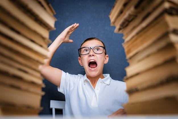 Chico inteligente feliz en vasos sentado entre dos pilas de libros y mirar hacia arriba sonriendo.