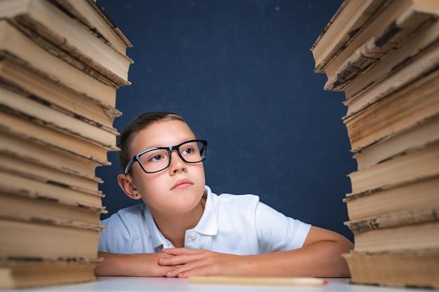 Chico inteligente con gafas sentado entre dos pilas de libros y apartar la mirada pensativamente.