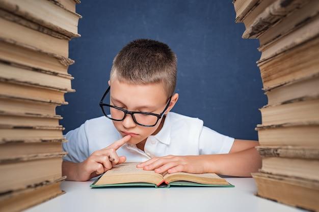 Chico inteligente con gafas sentado entre dos pilas de libros y leer el libro pensativamente.