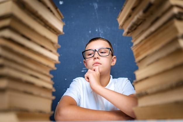 Chico inteligente con gafas sentado entre dos pilas de libros y mira hacia abajo pensativamente.