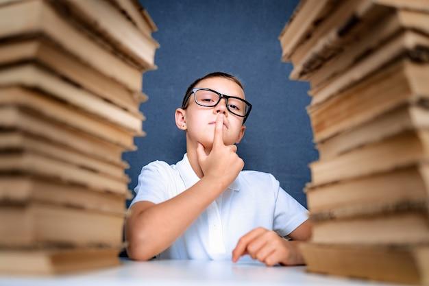 Chico inteligente con gafas sentado entre dos pilas de libros y mira a la cámara con un dedo en la boca.