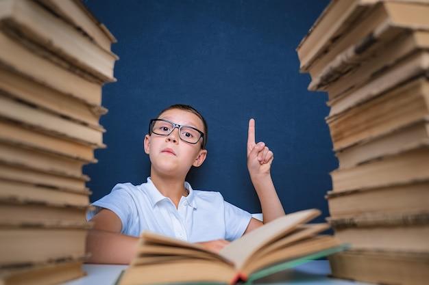 Chico inteligente con gafas sentado entre dos pilas de libros y mirar hacia arriba, señalando con el dedo.