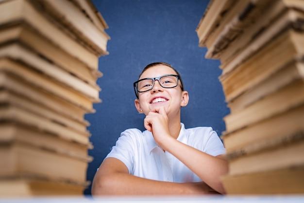 Chico inteligente con gafas sentado entre dos pilas de libros y mirar pensativamente.
