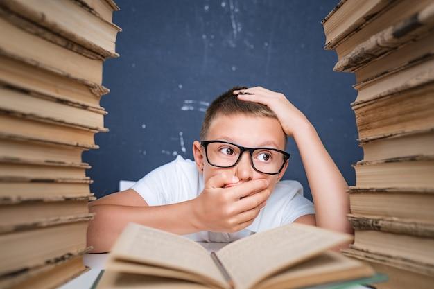 Chico inteligente con gafas volviéndose loco por leer un libro mientras está sentado entre dos pilas de libros.