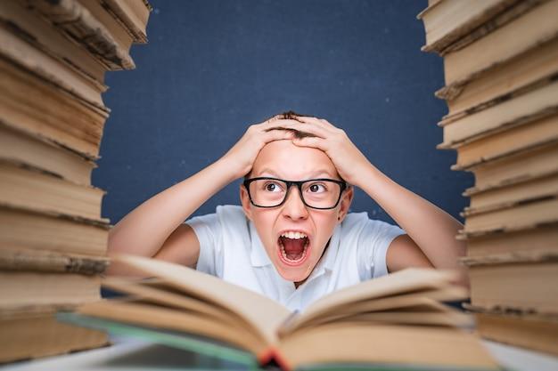 Chico inteligente con gafas volviéndose loco por leer un libro mientras está sentado entre dos pilas de libros