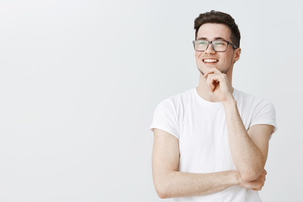 Chico inteligente pensativo con gafas mirando complacido a la izquierda, sonriendo de buena idea