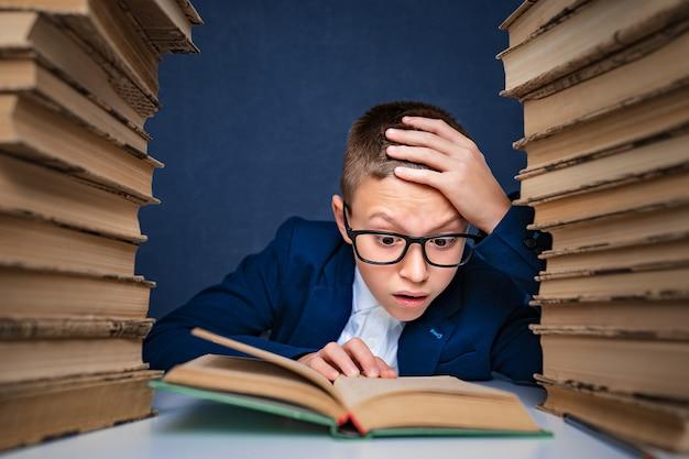 Chico inteligente en vasos sentado entre dos pilas de libros y leer el libro pensativamente