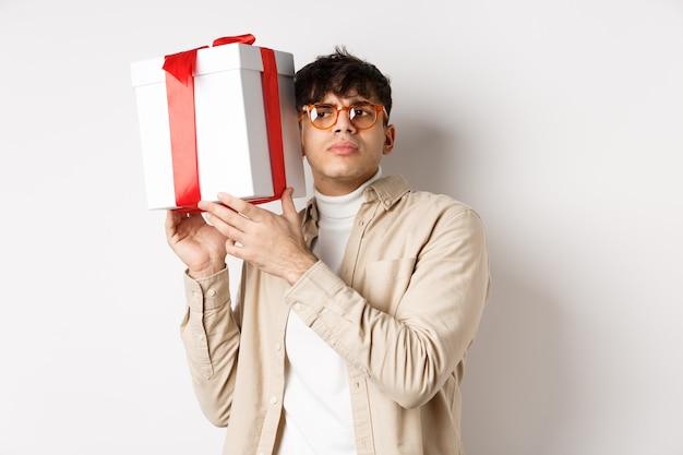 Chico intrigado escucha lo que hay dentro de la caja de regalo, tratando de adivinar el presente, de pie centrado en el fondo blanco.