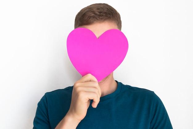 Chico irreconocible, joven cubre su rostro con valentine. copia espacio feliz día de san valentín. la persona anónima está ocultando la cara debajo de la tarjeta de felicitación en forma de corazón.