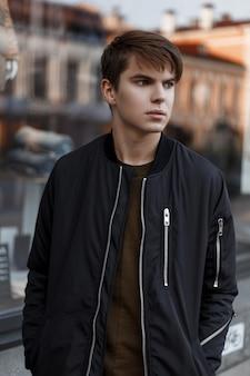 Chico joven americano con estilo en una chaqueta negra de moda en una camiseta con un peinado elegante en jeans está de pie cerca del escaparate. chico guapo de vacaciones.